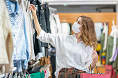 istock A young woman wears a protective mask while shopping at the Mall. 1224684241