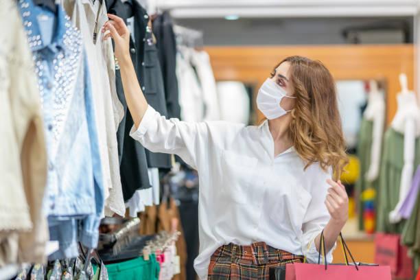 een jonge vrouw draagt een beschermend masker tijdens het winkelen in de mall. - kledingwinkel stockfoto's en -beelden