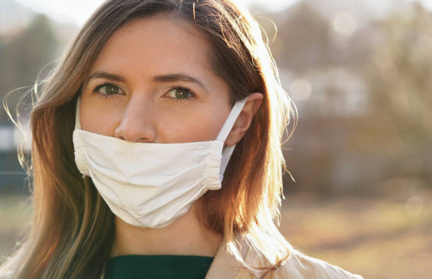 Young woman wears home made white cotton virus mouth face mask, wrong way, incorrect wearing - masks should cover nose as well stock photo