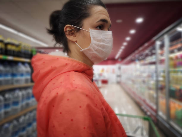 Young woman wears medical mask against virus while grocery shopping in supermarket, stock photo