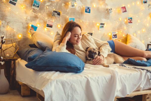 evde genç kadın hafta sonu köpek ile yalan yatak odası dekore - k logo stok fotoğraflar ve resimler