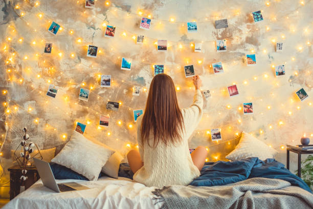 Young woman weekend at home decorated bedroom nostalgia Young woman creative weekend at home sitting looking at the photos on lighted wall memories nostalgia girl bedroom stock pictures, royalty-free photos & images