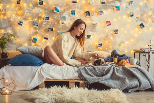 ev dekore yatak odasında genç kadın hafta sonu bir köpek scretching - k logo stok fotoğraflar ve resimler