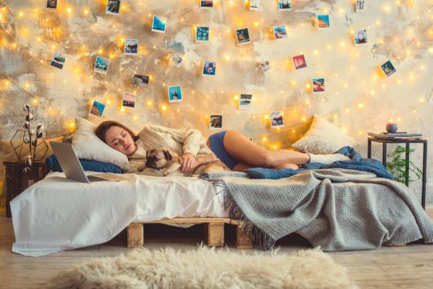 evde genç kadın hafta sonu bir köpek ile uyku yatak odası dekore - k logo stok fotoğraflar ve resimler