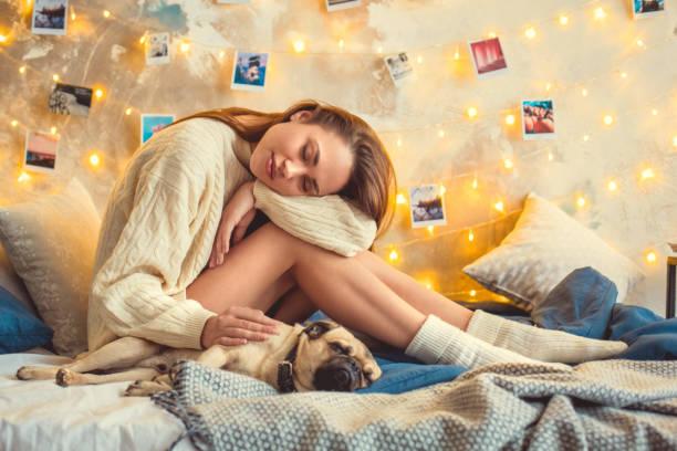 evde genç kadın hafta sonu diz üzerinde uyuyan köpek ile yatak odası dekore - k logo stok fotoğraflar ve resimler