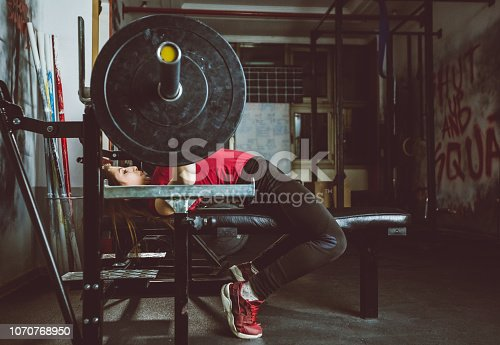 Young woman lifting barbell weights in a gym