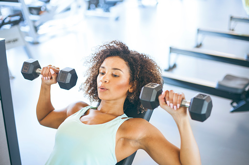 istock Young Woman Weightraining at the Gym 874837090