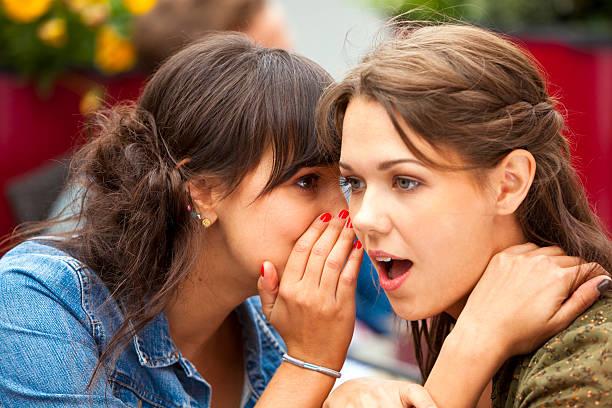囁く若い女性の秘密に他の人の耳にある cafe - 談笑する ストックフォトと画像