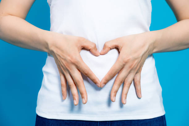 young woman who makes a heart shape by hands on her stomach. stock photo