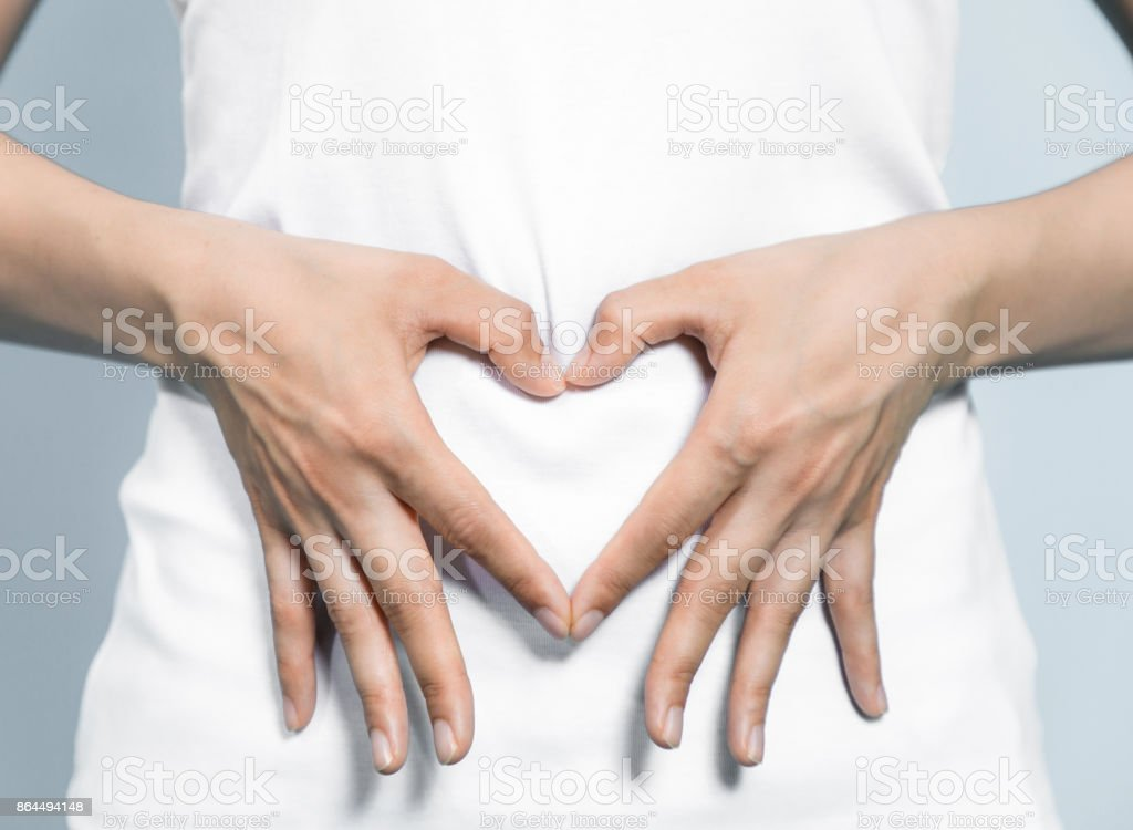 young woman who makes a heart shape by hands on her stomach. royalty-free stock photo
