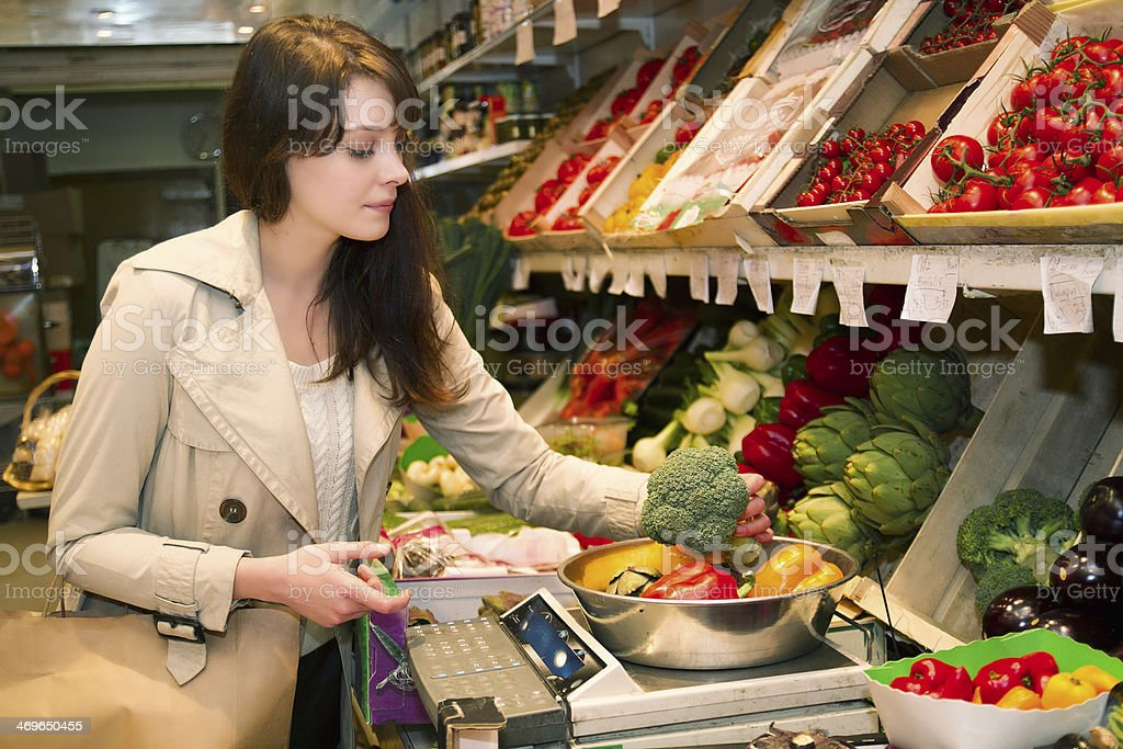 Young woman who weighs vegetables that it is buying stock photo