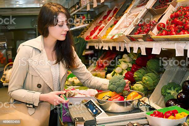 Young Woman Who Weighs Vegetables That It Is Buying Stock Photo - Download Image Now