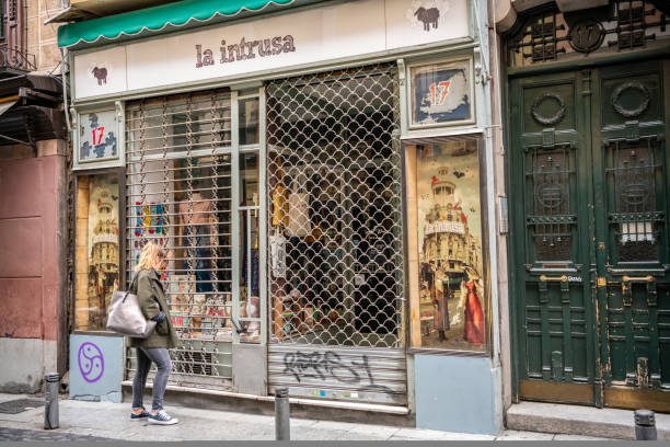 A young woman window shops at a vintage store in the Las Letras / Huertas neighborhood in Madrid. stock photo