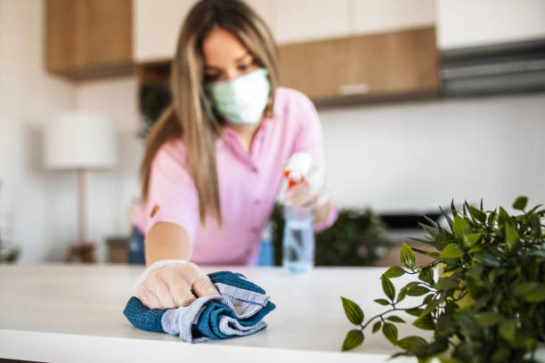 Young woman wiping kitchen counter stock photo