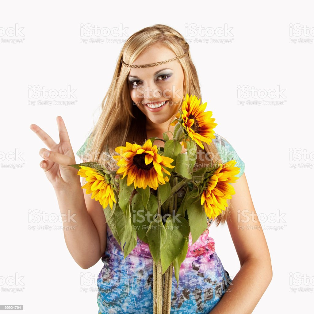 Young Woman With 1960's Style Tie-Dyed Shirt and Sunflowers royalty-free stock photo