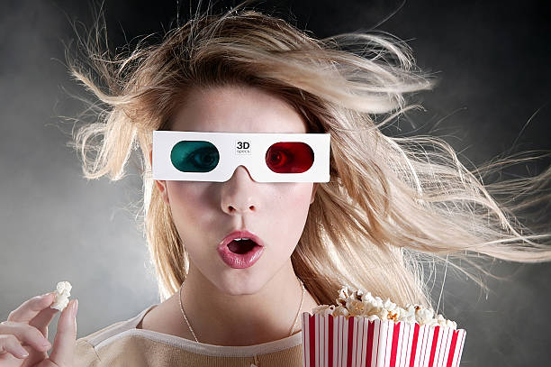 young woman with 3D movie glasses and popcorn stock photo