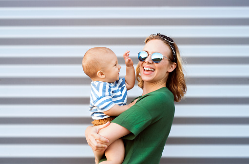 Young woman with a baby boy standing against the wall.