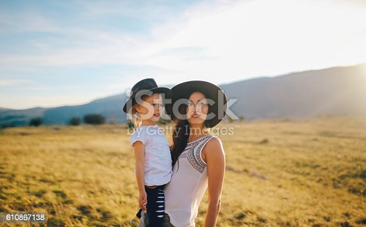 Portrait of a young fashionable woman with her baby girl in the beautiful nature outdoors. They are enjoying the view as the sun sets over the mountain range in the Dinaric Alps on the Croatian border, in the Southern Europe. They're wearing fashionable hippie clothes, hats, enjoying the time together.