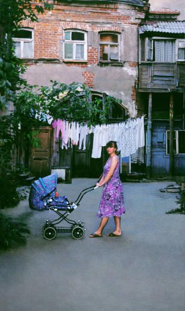 eine junge frau mit dem kinderwagen im innenhof des alten russischen haus der zeit des russischen reiches - typisch 90er stock-fotos und bilder
