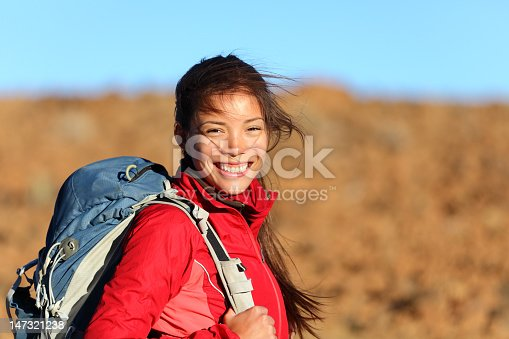 Healthy lifestyle xwoman hiker smiling happy outside on hiking trip. Beautiful natural candid smile on mixed race Caucasian / Asian female hiker outdoors in nature.