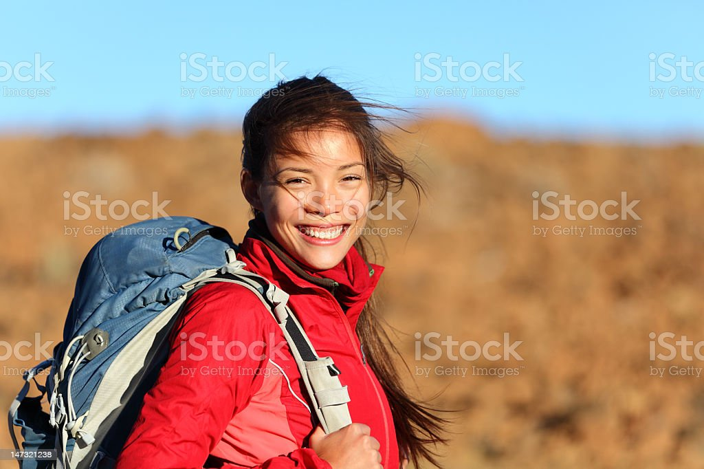 Young woman with a backpack smiling at camera stock photo