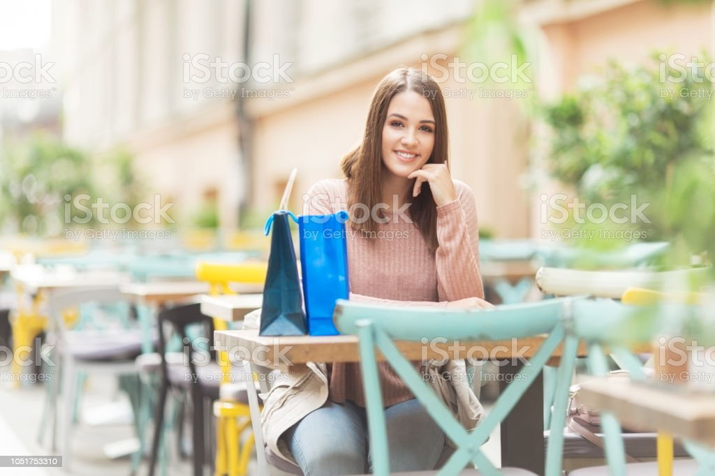 Young woman with a bag sitting in a cafe outdoors and smiling stock photo