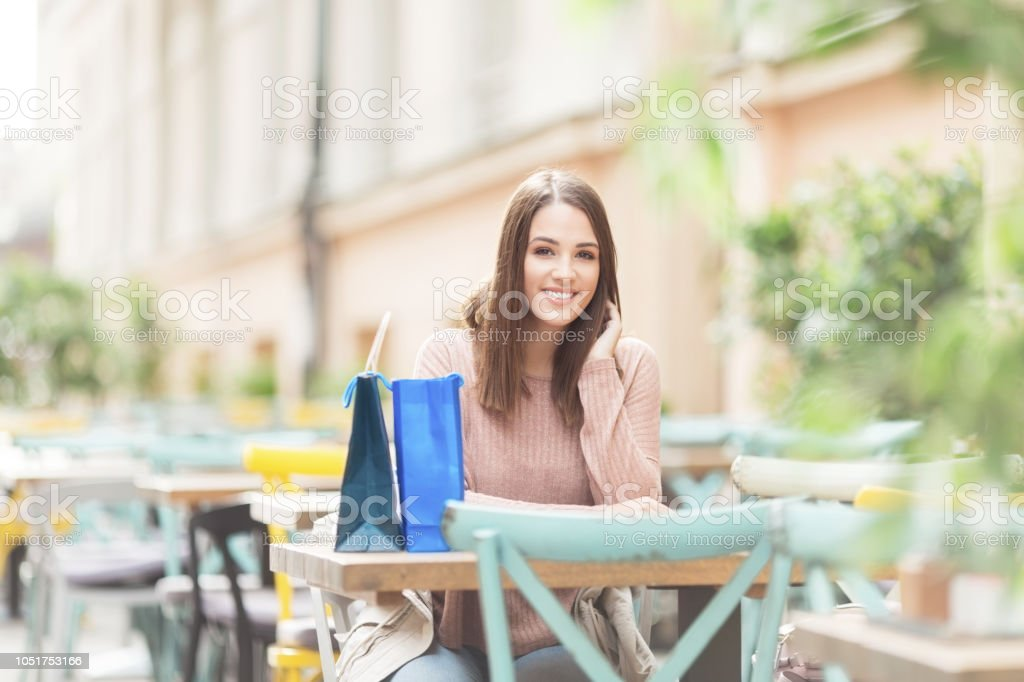 Young woman with a bag sitting in a cafe outdoors stock photo