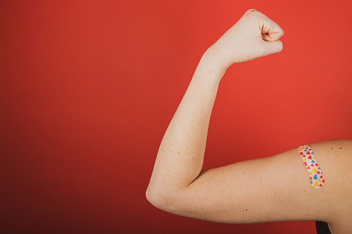 A girl makes a fist and flexes her bicep in front of a red background while wearing a bandage with hearts on it indicating she has received the Coronavirust, Covid-19 vaccination during the pandemic
