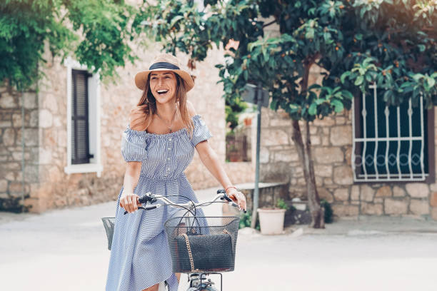 Young woman with a bicycle in a Greek town stock photo