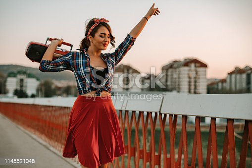 Playful retro styled woman with a boom box listening to music on a sunny summer day