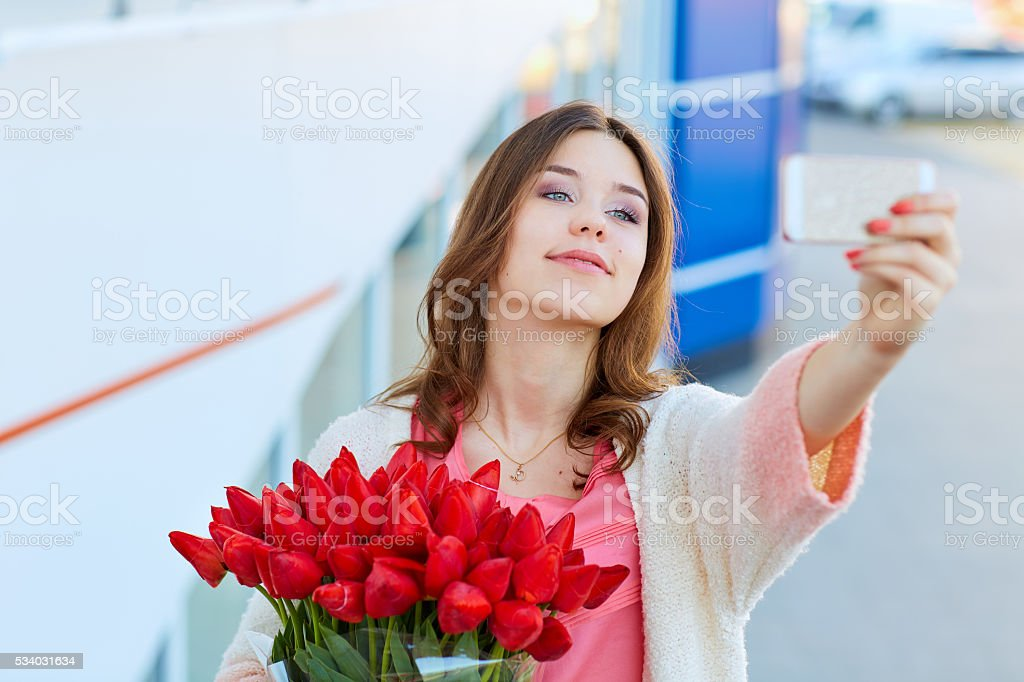 Young  woman with a bouquet  is taking selfie stock photo