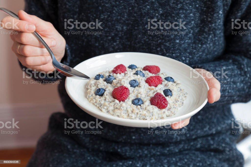Junge Frau mit einer Schüssel Haferflocken mit Berrias. Mädchen mit Haferflocken, Himbeeren, Heidelbeeren, Chia-Samen und Honig in einer Schüssel zu frühstücken. Mädchen hält Helthy hausgemachtes Frühstück. Gesunde Snacks und Frühstück am Morgen. – Foto