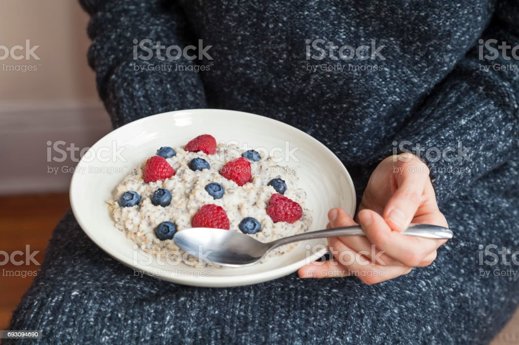 Young woman with a bowl of oatmeal with  berrias. Girl eating breakfast with oatmeal,  raspberries, blueberries, chia seeds and honey  in a bowl. Girl holding helthy homemade breakfast. Healthy snack or breakfast in the morning. stock photo