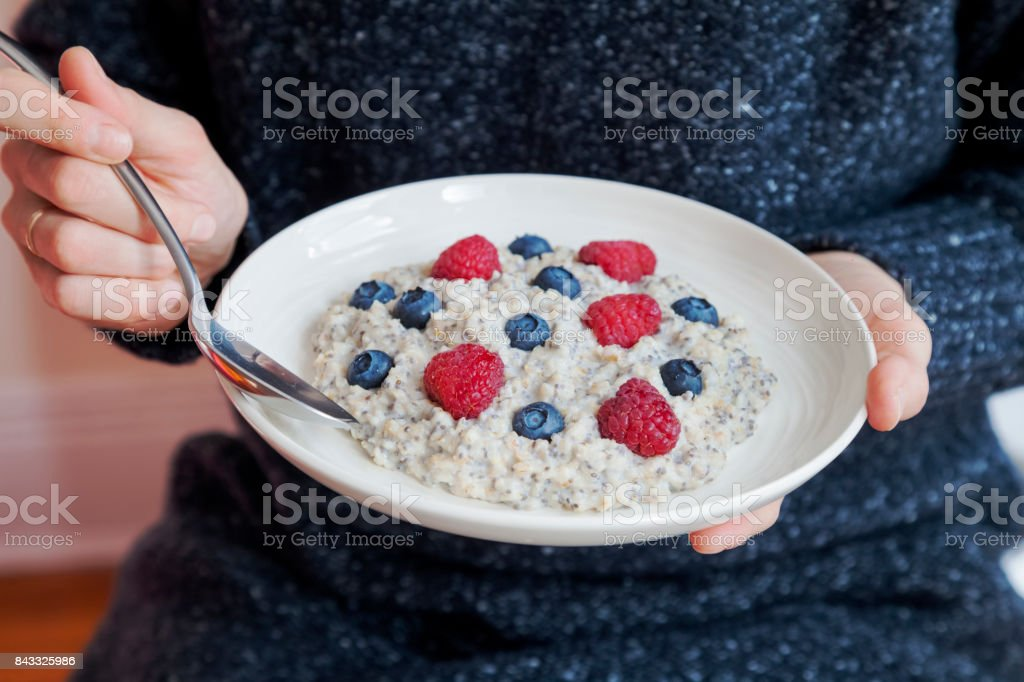 Young woman with a bowl of oatmeal with  berries. Girl eating breakfast with oatmeal, raspberries, blueberries, chia seeds and honey  in a bowl. Girl holding helthy homemade breakfast. Healthy snack or breakfast in the morning. stock photo