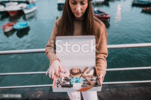 Young woman with a box full of doughnuts