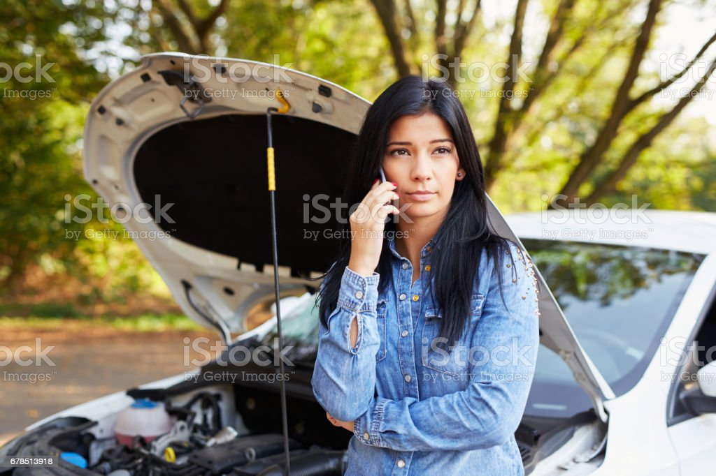 Young woman with a broken car foto
