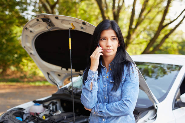 Young woman with a broken car​​​ foto