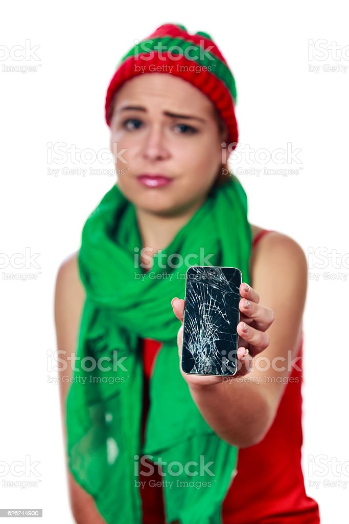 Young woman with a broken smartphone on christmas stock photo