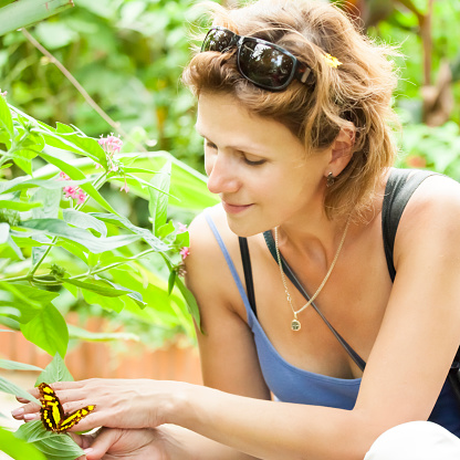 Young beautiful women having butterfly sitting on hand