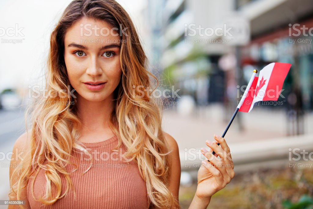 Young Woman with a Canadian Flag Outside Portrait stock photo