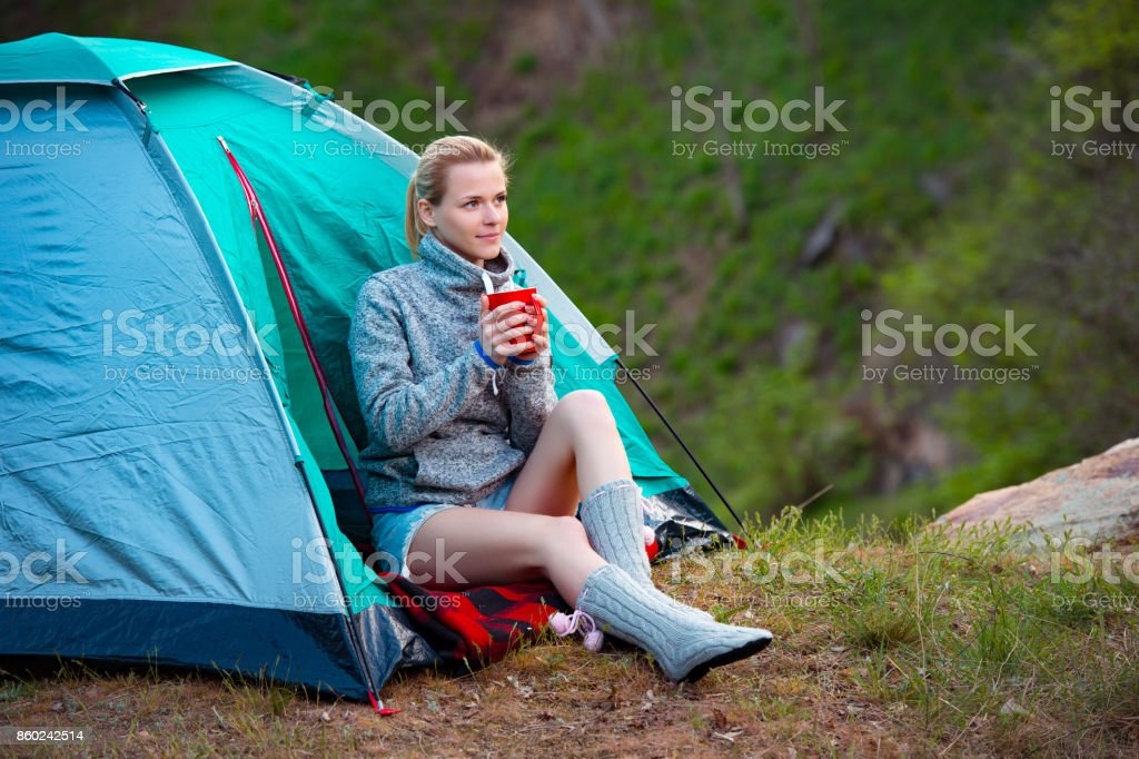 Young woman with a cup of tea near a tent against green forest background, Camping, travel, tourism, hike and people concept stock photo