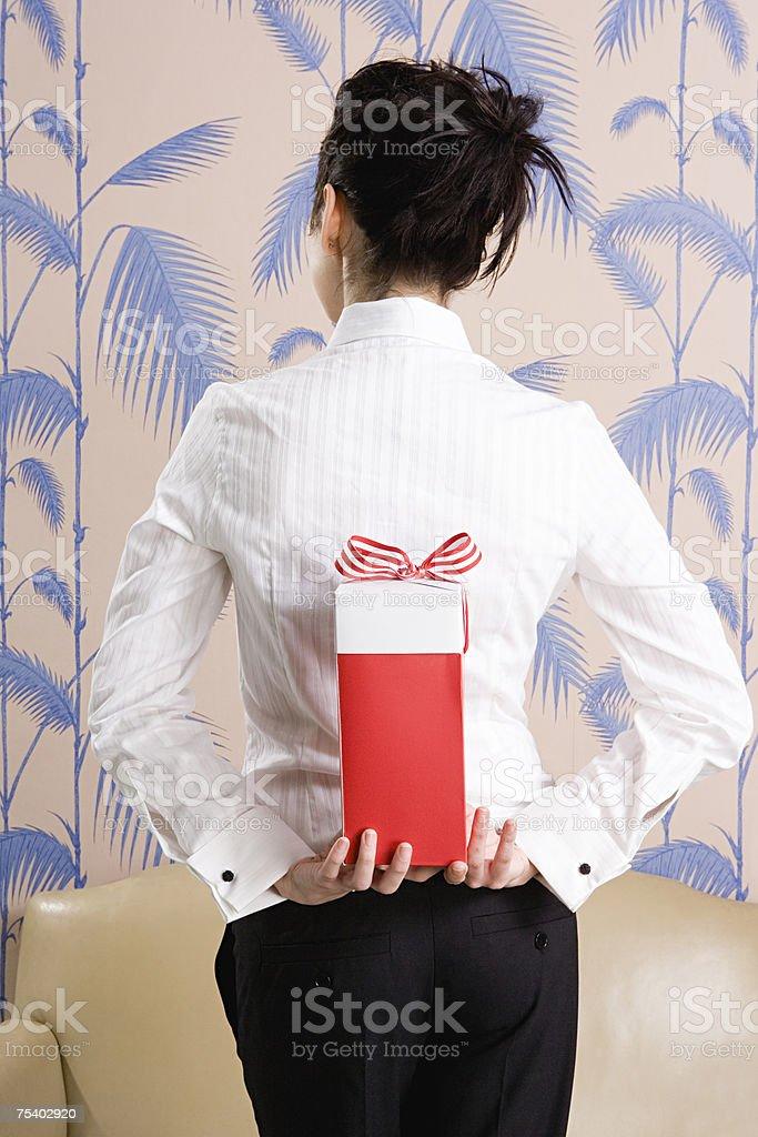 Jovem mulher com um presente atrás da sua parte de trás foto de stock royalty-free