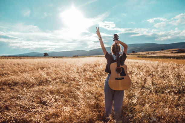 Young woman with a guitar on a sunny day in field stock photo
