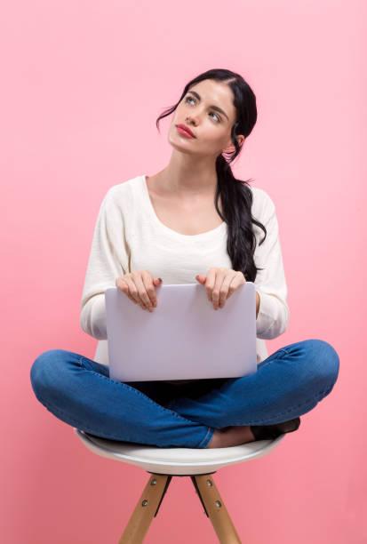 Junge Frau mit einem Laptop in einer nachdenklichen Pose – Foto