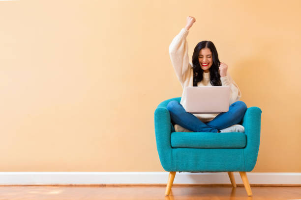 Young woman with a laptop computer with successful pose Young woman with a laptop computer with successful pose sitting in a chair yay stock pictures, royalty-free photos & images