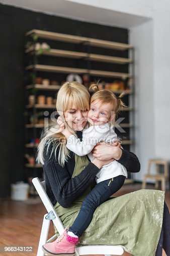 istock A young woman with a little daughter relaxing in creative studio. Mother and her small kid sitting on chair. 966343122