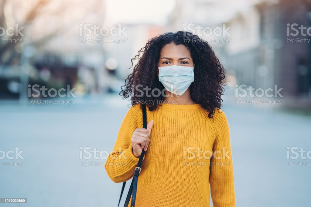 Young woman with a mask during pandemic Woman wearing a face mask walking outdoors 2020 Stock Photo