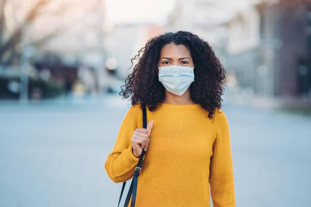 パンデミック中にマスクを持つ若い女性 - マスク ストックフォトと画像