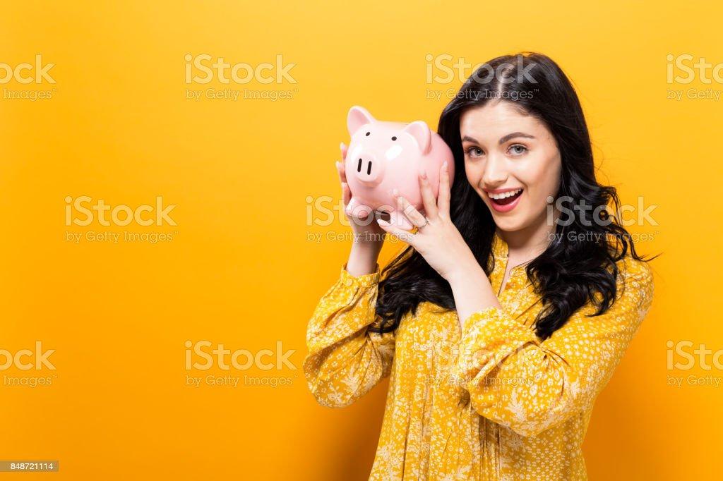 Junge Frau mit einem Sparschwein – Foto
