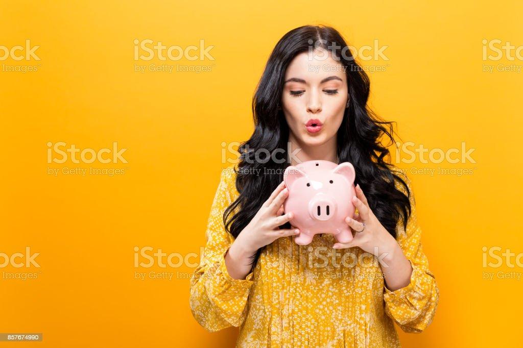 Mujer joven con una alcancía - foto de stock